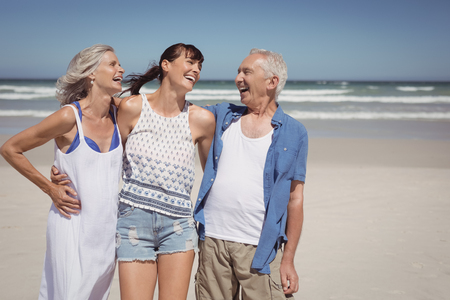 Cheerful family standing at beach during sunny day