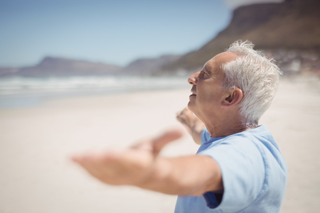 Side view of senior man with arms outstretched standing at beach