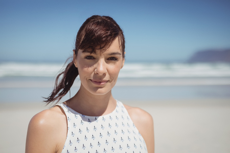Portrait of young woman standing at beach during sunny day Stock Photo
