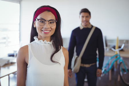 Happy young businesswoman standing with male colleague in background at office Stock Photo
