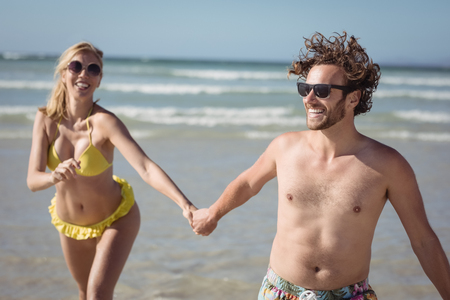 Happy couple holding hands while running at beach during sunny day