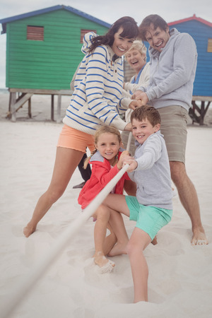 Happy multi-generation family playing tug of war at beach Stock Photo