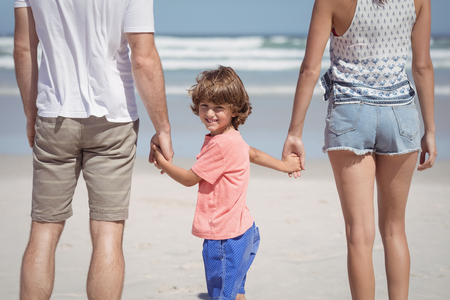 Portret van de handen van de jongensholding terwijl status met ouders bij strand