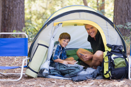 Portrait of happy father and son sitting inside tent while hiking in forest