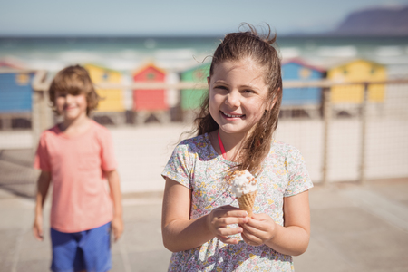 Portrait of smiling girl holding ice cream with brother standing in background at beach during sunny day