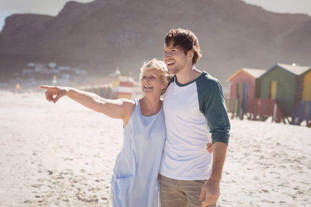 Happy woman pointing away with her son standing at beach during sunny day Stock Photo