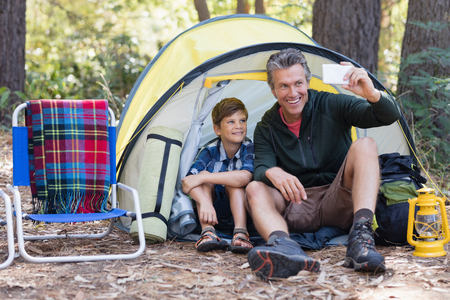 adventuring: Smiling father and son taking selfie while sitting in tent