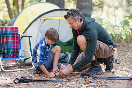 campsite: Father helping son to wear sandals by tent in forest Stock Photo