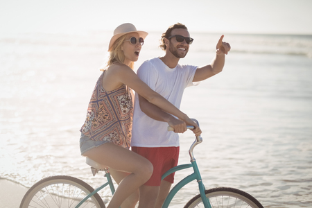 Happy couple riding bicycle at beach during sunny day Stock Photo