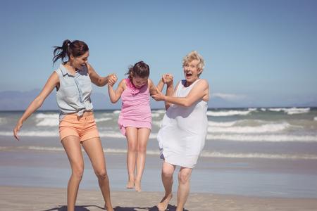 Het vrolijke familie van meerdere generaties spelen bij strand tijdens zonnige dag