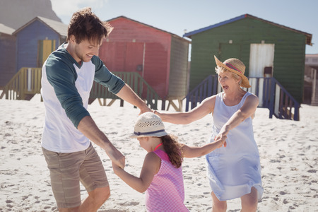 Happy multi-generation family holding hands at beach during sunny day