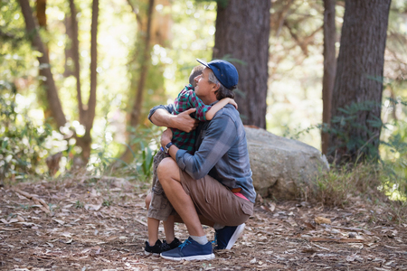 Side view of father and son embracing while hiking in forest Stock Photo