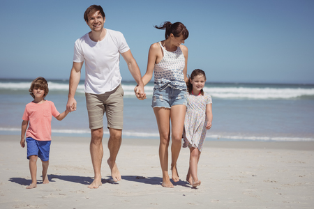 holding hands while walking: Happy man walking with his family while holding hands at beach during sunny day Stock Photo