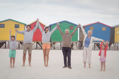Portrait of cheerful multi-generation family holding hands while standing at beach