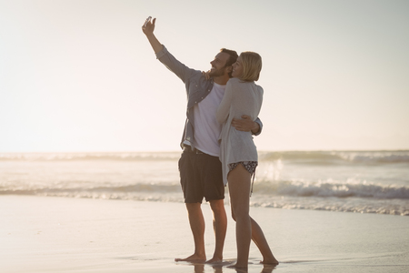Young couple taking selfie on shore at beach during sunny day