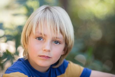 Chiuda sul ritratto del ragazzino sveglio in foresta Archivio Fotografico - 77599162