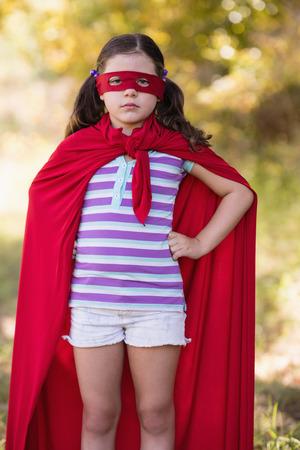 pinata: Portrait of confident little girl wearing superhero costume at campsite Stock Photo
