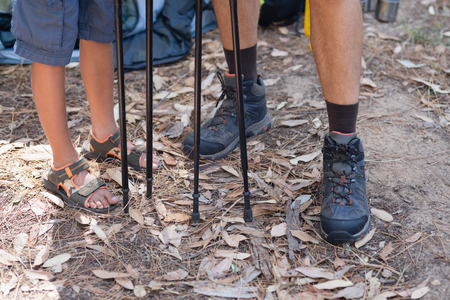 Low section of father and son with hiking poles standing in forest