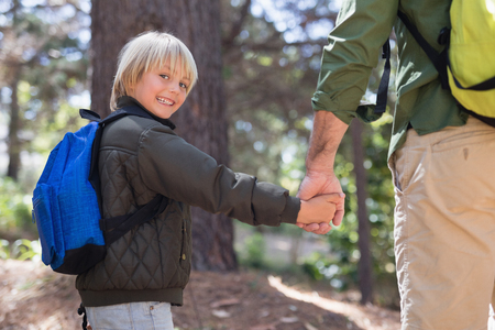 Portrait of happy boy holding fathers hand while hiking in forest Stock Photo