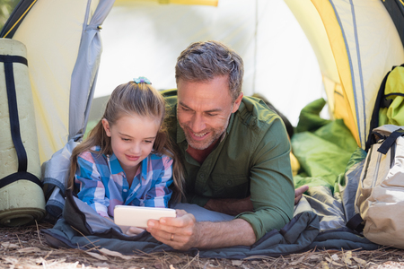 Father and daughter using mobile phone while resting in tent at campsite