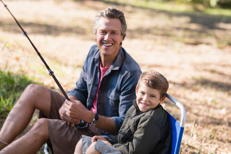 Portrait of cheerful father and son fishing on sunny day