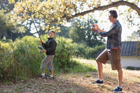 sacar la lengua: Father photographing son posing with fishing rod in forest