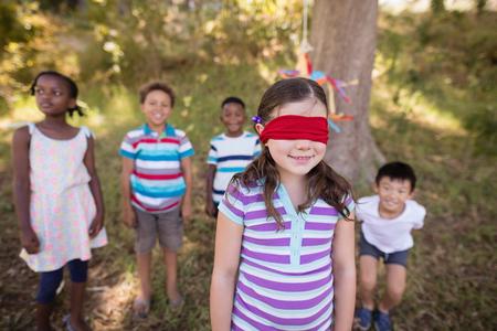 Amigos que miran la muchacha con los ojos vendados que se coloca en campo herboso en bosque
