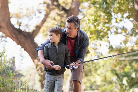 adventuring: Father and son fishing on sunny day in forest Stock Photo