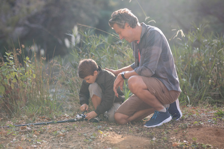 Father and son with fishing rod kneeling on field during sunny day Reklamní fotografie