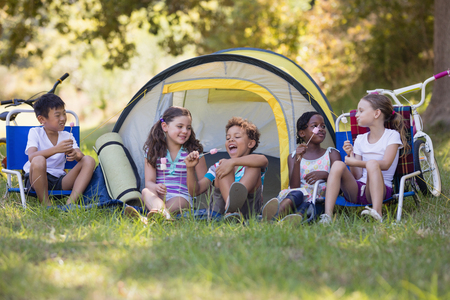 Group of happy friends eating candies while sitting outside tent at campsite Stock Photo