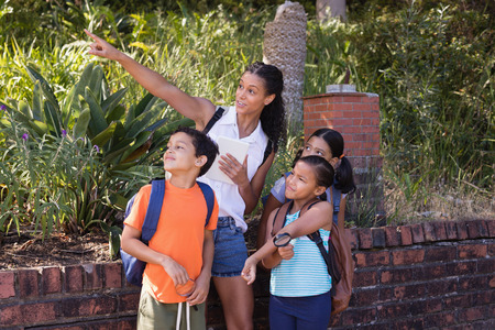 finding out: Teacher pointing to children at nature reserve during field trip