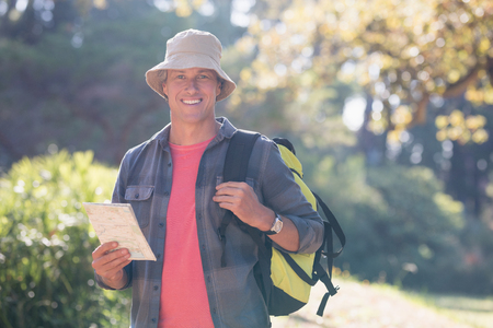 using binoculars: Portrait of happy male hiker with map standing in forest Stock Photo