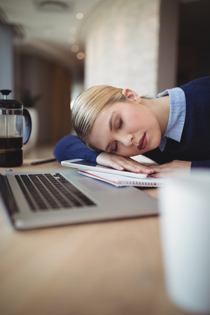 overburden: Tried executive sleeping at desk in office Stock Photo