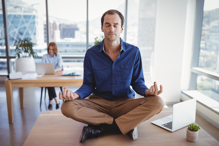 Executive meditating on desk with her colleague working in background