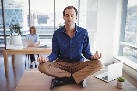 Exekutive, die auf Schreibtisch mit ihrem Kollegen arbeitet im Hintergrund meditiert Standard-Bild - 77600407