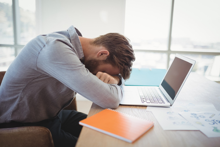 overburden: Tired executive leaning on desk in office Stock Photo