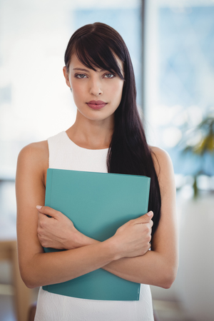 Portrait of beautiful executive holding file in office Stock Photo