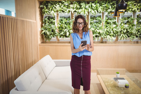 Smiling executive using mobile phone in office