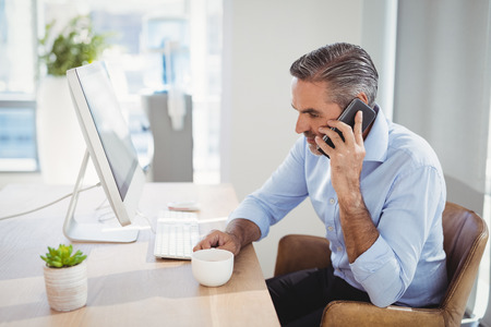 Executive talking on mobile phone at desk in office