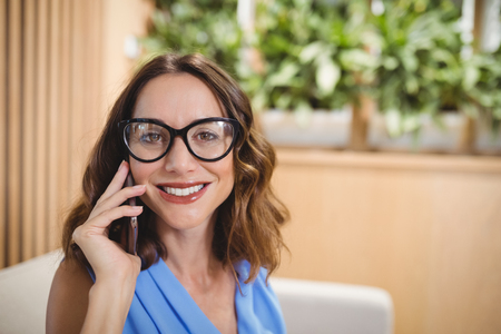 Portrait of executive talking on mobile phone in office