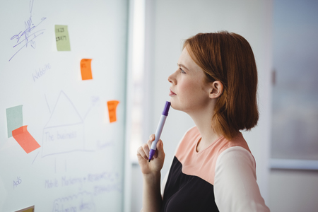 Thoughtful executive reading sticky note in office Imagens