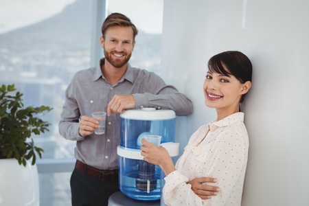 Portrait of smiling executives holding glasses of water in office 스톡 콘텐츠