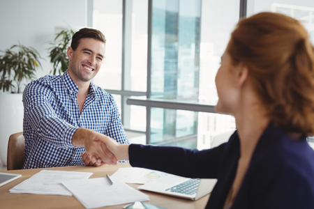 Smiling executives shaking hands at desk in office Stock Photo