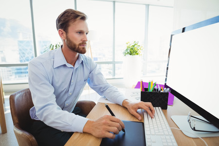 Attentive graphic designer working at desk in office
