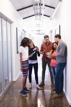 businesswear: Business people using technologies while standing in corridor