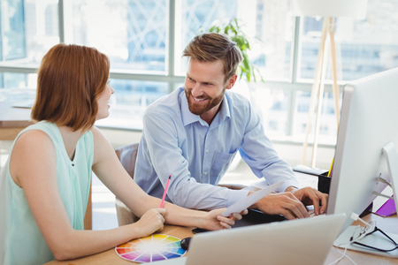 Smiling graphic designers interacting while working at desk in office