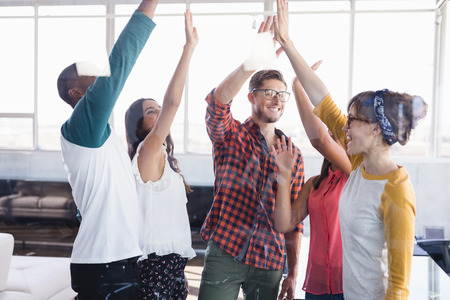 businesswear: Cheerful business people doing high five while standing in office seen through glass Stock Photo