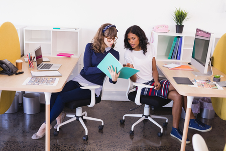 businesswear: Businesswomen discussing while working at desk in office Stock Photo