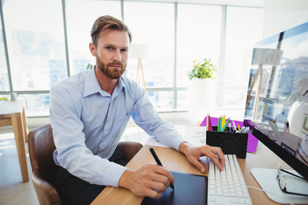 Portrait of executive working at desk in office