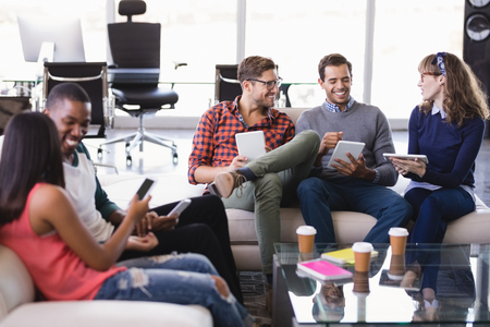 businesswear: Smiling business people discussing while sitting on sofa in office